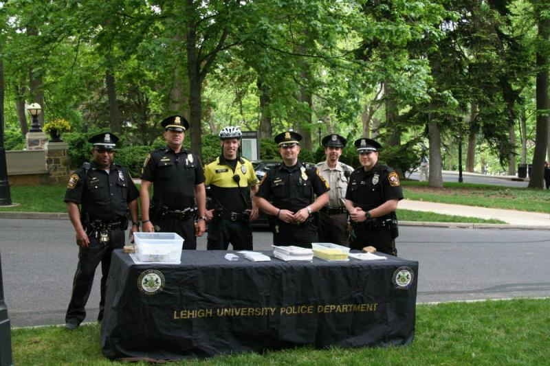 photo of officers standing behind info table on UC lawn